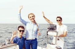 Groupe d'amis heureux ayant une partie sur un yacht et buvant le ch Image stock