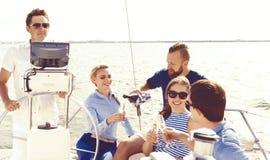 Groupe d'amis heureux ayant une partie sur un yacht et buvant le ch Photo libre de droits