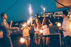 Groupe d'amis heureux célébrant au dessus de toit Photographie stock