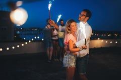 Groupe d'amis heureux célébrant au dessus de toit Images libres de droits