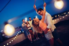 Groupe d'amis heureux célébrant au dessus de toit Image stock