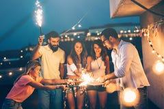 Groupe d'amis heureux célébrant au dessus de toit Photographie stock libre de droits