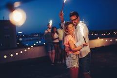 Groupe d'amis heureux célébrant au dessus de toit Photo stock