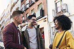 Groupe d'amis heureux causant dans la rue Photographie stock