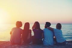 Groupe d'amis heureux détendant à la plage Image stock