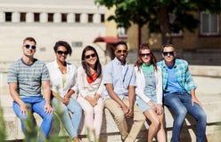 Groupe d'amis heureux dans des lunettes de soleil dans la ville Images stock
