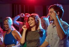 Groupe d'amis heureux dansant dans la boîte de nuit Images libres de droits