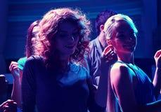 Groupe d'amis heureux dansant dans la boîte de nuit Photo stock