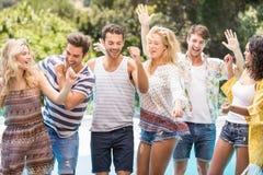 Groupe d'amis heureux dansant près de la piscine Images libres de droits