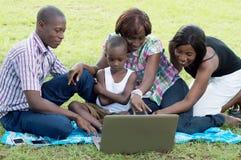 Groupe d'amis heureux devant un ordinateur portable Photographie stock