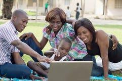 Groupe d'amis heureux devant un ordinateur portable Images stock