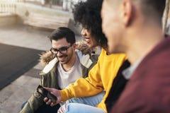 Groupe d'amis heureux employant le mobile dans la rue Images stock