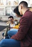 Groupe d'amis heureux employant le mobile dans la rue Image stock