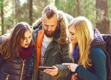 Groupe d'amis heureux et jeunes signant une carte sur un smartphone Photographie stock