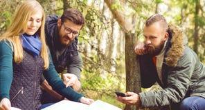 Groupe d'amis heureux et jeunes vérifiant une carte dans le camp de forêt, à Photographie stock libre de droits