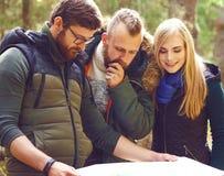 Groupe d'amis heureux et jeunes vérifiant une carte dans le camp de forêt, à Images libres de droits