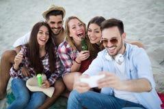 Groupe d'amis heureux faisant la fête sur la plage Images libres de droits