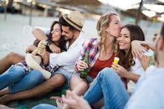 Groupe d'amis heureux faisant la fête sur la plage Images stock
