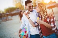 Groupe d'amis heureux faisant la fête sur la plage Image stock