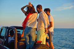 Groupe d'amis heureux faisant la partie dans les jeunes automobiles ayant le champagne potable d'amusement Photos libres de droits