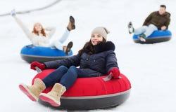 Groupe d'amis heureux glissant vers le bas sur des tubes de neige Photo stock