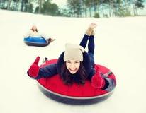 Groupe d'amis heureux glissant vers le bas sur des tubes de neige Photographie stock