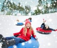 Groupe d'amis heureux glissant vers le bas sur des tubes de neige Photo libre de droits