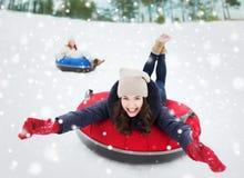 Groupe d'amis heureux glissant vers le bas sur des tubes de neige Image stock