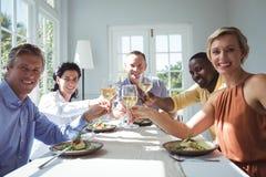 Groupe d'amis heureux grillant des verres de vin Photographie stock
