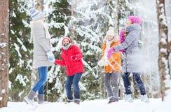 Groupe d'amis heureux jouant des boules de neige dans la forêt Photos stock