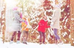 Groupe d'amis heureux jouant des boules de neige dans la forêt Images stock