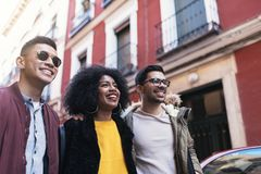 Groupe d'amis heureux marchant dans la rue Photos stock