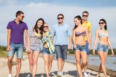 Groupe d'amis heureux marchant le long de la plage Photographie stock