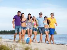 Groupe d'amis heureux marchant le long de la plage Image stock