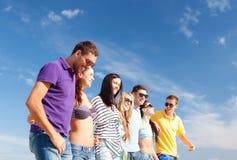 Groupe d'amis heureux marchant le long de la plage Photo libre de droits