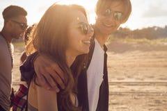 Groupe d'amis heureux marchant sur la plage Photographie stock libre de droits