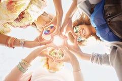Groupe d'amis heureux montrant des coeurs photographie stock