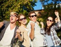 Groupe d'amis heureux montrant le geste de triomphe Image stock