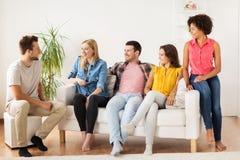 Groupe d'amis heureux parlant à la maison Image stock
