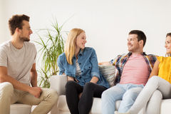 Groupe d'amis heureux parlant à la maison Photo stock
