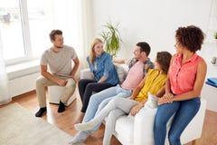 Groupe d'amis heureux parlant à la maison Photo libre de droits