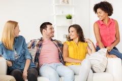 Groupe d'amis heureux parlant à la maison Photographie stock