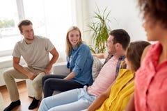 Groupe d'amis heureux parlant à la maison Photos stock