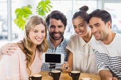 Groupe d'amis heureux prenant la photo avec le bâton de slefie Photo stock