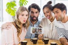 Groupe d'amis heureux prenant la photo avec le bâton de slefie Image libre de droits