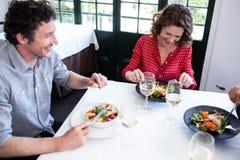 Groupe d'amis heureux prenant le déjeuner dans le restaurant Images stock