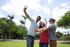 Groupe d'amis heureux prenant le selfie Photos stock