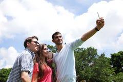 Groupe d'amis heureux prenant le selfie Photo stock
