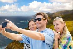 Groupe d'amis heureux prenant le selfie par le téléphone portable Photographie stock libre de droits