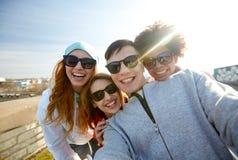 Groupe d'amis heureux prenant le selfie sur la rue Photographie stock